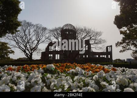 silhouette of Hiroshima Peace Memorial(Genbaku Dome) with flowers in spring, Naka Ward, Hiroshima, Japan - Stock Photo