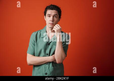 Image of confused caucasian man posing and looking at camera isolated over red background