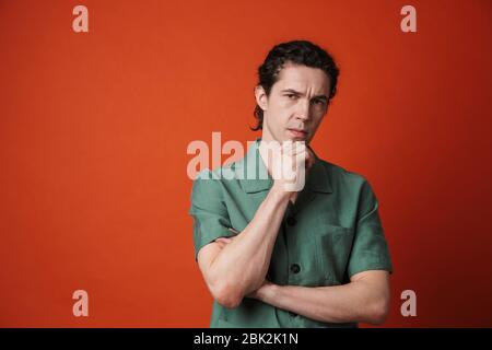 Image of displeased caucasian man posing and looking at camera isolated over red background
