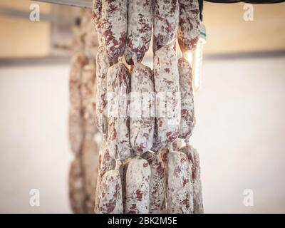 French saucission drying and hanging in a kitchen. Saucisson, or saucisse seche, is a traditional dry sausage made of cured meat from France.  Picture - Stock Photo