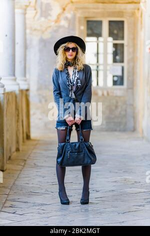 Teengirl with blond curls hair wide hat and sunglasses standing facing at camera frontal view serious in corridor photogenic personality - Stock Photo
