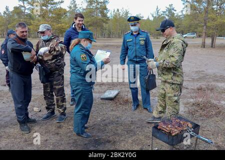 Yakutsk, Russia. 1st May, 2020. Officers of the Russian State Fire Service on patrol; a state of fire emergency not yet declared in Yakutsk, Emercom inspectors in cooperation with the police, forestry workers and municipal officials brief citizens on wildfire safety measures and requirements, hand out checklists. Credit: Yevgeny Sofroneyev/TASS/Alamy Live News