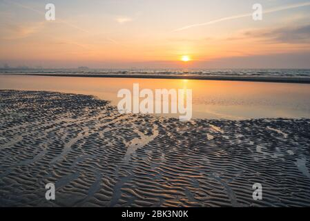 Sun sets behind a cloud bank over the North Sea. Beautiful reflection of colors in the wet sand.