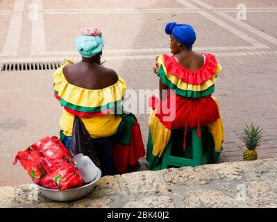 Cartagena, Colombia, August 1 2019: two tipical fruit street sellers palenqueras with colorful dresses seated resting from the back