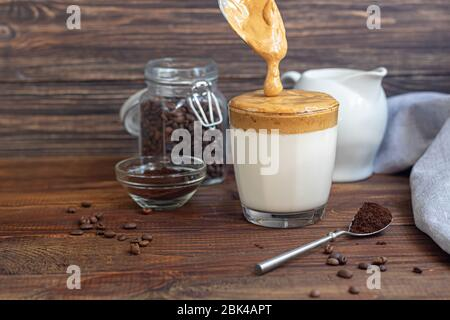 Dalgona coffee is a trendy cold Korean drink. Tasty, aromatic coffee with milk and sugar in a glass on a wooden background. Copy space - Stock Photo