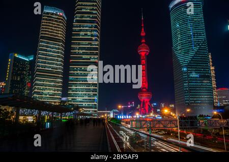 The Oriental Pearl Tower seen at night from the skywalk in Lujiazui in the Pudong New Area of Shanghai, China. - Stock Photo