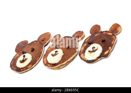 Flat lay composition with pancakes in form of bear isoleted on white background. Creative breakfast ideas for kids. - Stock Photo