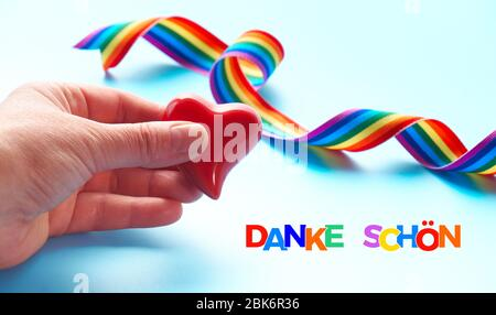 Rainbow text 'Danke shon' in German means 'Thank you' in English language. Hand holding heart, rainbow ribbon. Symbols of public gratitude for doctors - Stock Photo