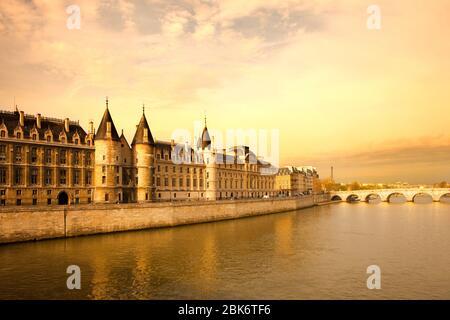 The Conciergerie at Justice Palace and Pont Neuf Bridge over the Seine River, Ile de la Cite, Paris, France - Stock Photo