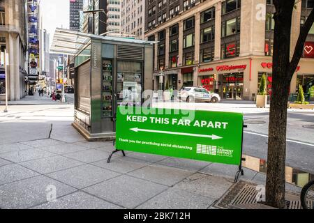 New York City, New York, USA - April 20, 2020:  View of empty street in Manhattan with sign warning to keep social distancing during the Covid-19 Coro - Stock Photo