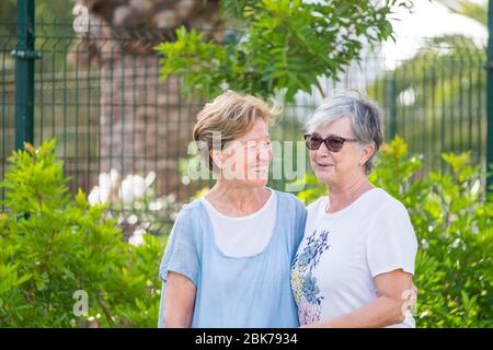 Senior couple female caucasian friends have fun and enjoy social contact and friendship outdoor after lockdown for coronavirus and are happy for healt - Stock Photo