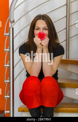 Teengirl brunette hair posing in living room wearing fanciful Black and Red clothing - Stock Photo