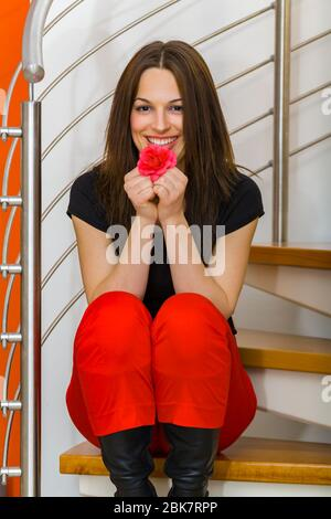 Teengirl brunette hair posing in living room wearing fanciful Black and Red clothing excited excitement joy joyful - Stock Photo