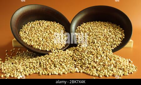 Buckwheat scattered background, raw green buckwheat in a brown clay bowl or plate. Healthy groats. Organic raw non-fried vegetarian food. The concept - Stock Photo