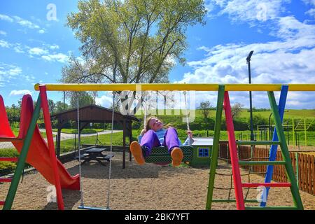 Child playing on outdoor playground. Kid play on school or kindergarten yard. Active kid on colorful swing. Healthy summer activity for children in