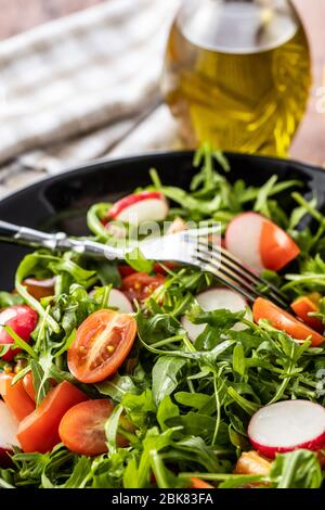 Fresh arugula salad with radishes, tomatoes and red peppers on plate.