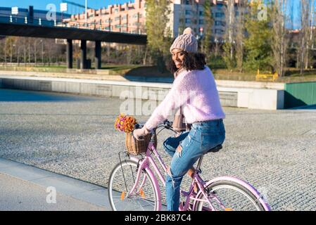 Black young woman riding a vintage bicycle with flowers - Stock Photo