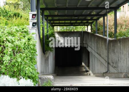 One lane entrance and exit of an underground concrete garage or parking of a residential building.
