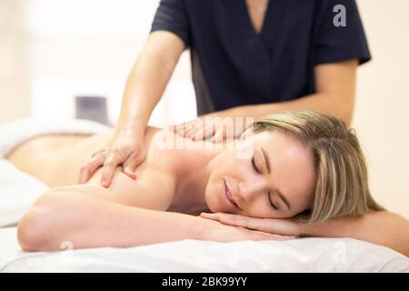 Woman lying on a stretcher receiving a back massage.