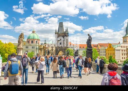 Prague, Czech Republic, May 13, 2019: people are walking down cobblestone pedestrian Charles Bridge Karluv Most over Vltava river, Prague Old Town Bridge Tower and St. Salvator Church background