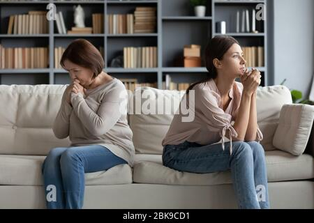 Stubborn adult daughter and mature mother ignoring each other - Stock Photo