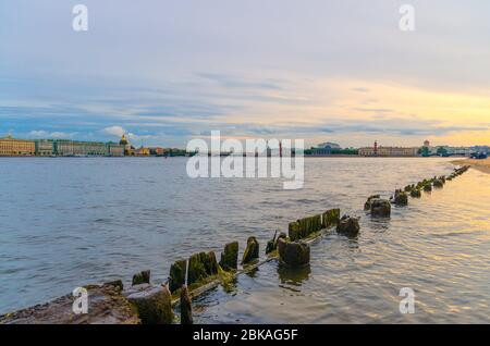 Wooden fence in Neva river water on Zayachy Hare Island, cityscape of Saint Petersburg Leningrad, Winter Palace, State Hermitage Museum, Saint Isaac's Cathedral, Arrow of Vasilyevsky Island, Russia - Stock Photo