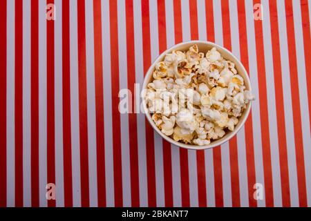 Top view of popcorn in bowl on striped background