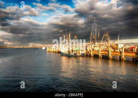 Various boats docked at Macmillan wharf in Provincetown Massachusetts on Cape Cod Bay at sunset. - Stock Photo