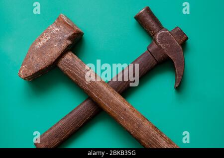 Crossed vintage hammers on a turquoise background. Two old rusty hammers on a colored background. Hand tools and labor. Place for text. Top view at an