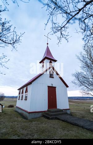 Typical red colored wooden church in Fludir town in south Iceland within the Golden Circle. Sunset light stock picture