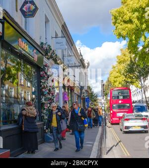 Londoners and tourists shop on Pembridge Rd, Notting Hill, London England. Double decker bus passes in the street. - Stock Photo