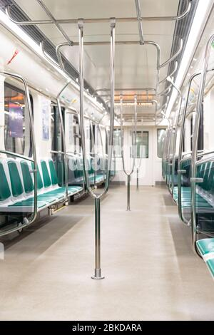 Empty train seats of subway train during coronavirus pandemic, selective focus on handrail. Strong decrease in passenger traffic in public transport d - Stock Photo