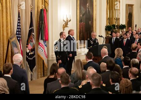 President Donald J. Trump presents the Medal of Honor to U.S. Army Master Sgt. Matthew O. Williams Wednesday, Oct. 30, 2019, in the East Room of the White House. Williams is receiving the honor for his actions during the April 2008 Battle of Shok Valley in the Nuristan Province of Afghanistan. President Trump Presents the Medal of Honor to U.S. Army Master Sgt. Matthew O. Williams - Stock Photo