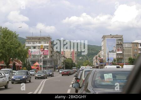 Driving through Baia Mare, Romania. Communist era apartment buildings on the side of the road. - Stock Photo