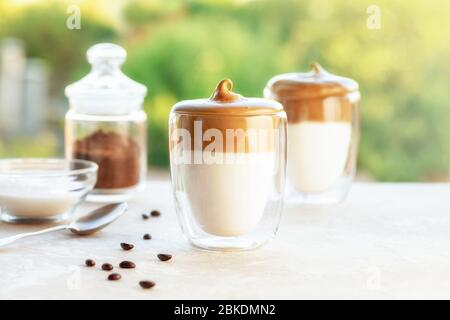Tasty homemade Dalgona coffee in glass cup with ingredients, coffee and suger on a table on green background. Recipe popular Korean drink latte with f - Stock Photo