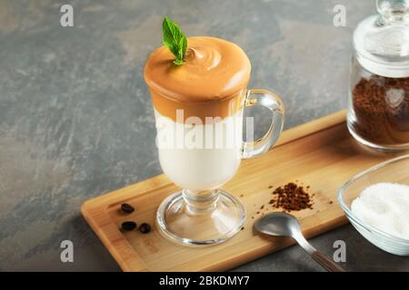 Dalgona frothy coffee in glass on wooden board on grey background. Trend korean Iced  latte coffee drink with foam of instant coffee with ingredients. - Stock Photo