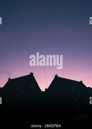 Black silhouette of the rooftops of two houses with chimneys and a pink blue panoramic sky background. The Hague, Netherlands, Europe. - Stock Photo