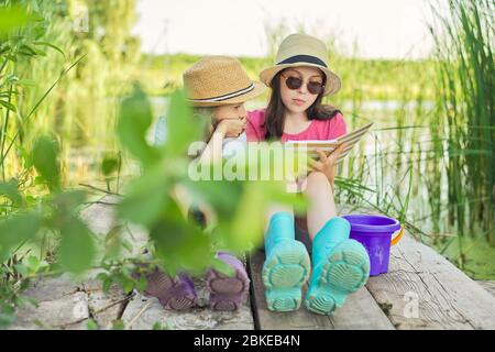 Children two girls resting playing reading their notebook in nature - Stock Photo