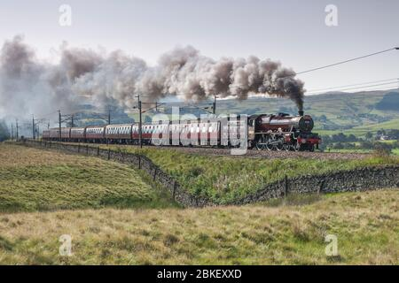 LMS Steam locomotive 5690 Leander passing Scout Green, Cumbria on the west coast mainline with a West Coast Railways operated steam charter train. - Stock Photo