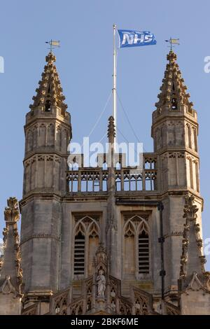 BATH, UK - APRIL 20, 2020 :  'THANK YOU NHS' Flag flying on Bath Abbey as a tribute to all the work of the National Health Service during COVID crisis - Stock Photo