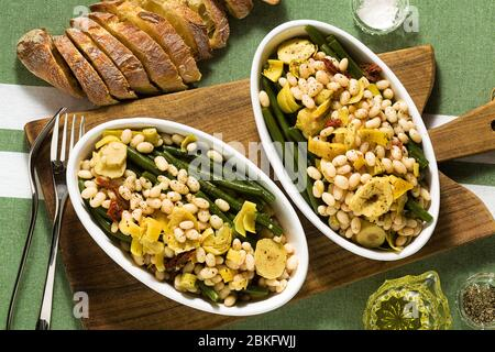 Cannellini nutritious white bean salad with green beans, sun-dried tomatoes and artichokes in oil. Traditional italian food - Stock Photo