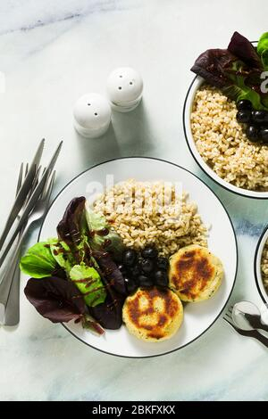 A simple vegan lunch or dinner for a family of two adults and a child. brown rice with soy okara and potato patties with fresh salad and olives on a m - Stock Photo