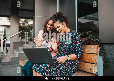 Two beautiful young women friends waving hand and talking while having a video call with their friends on a laptop in a city street. Stock Photo
