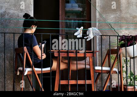 Young woman sat on her balcony using her smartphone.