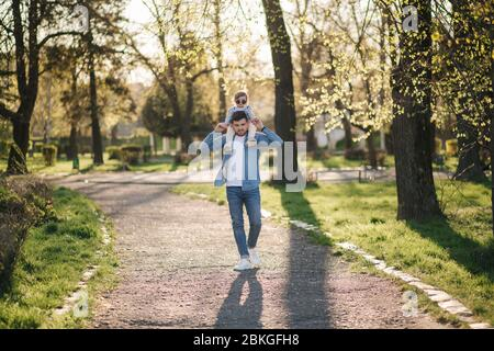 Adorable little daughter sitting on dad's neck and laughing. Young father walk with his cute daughter in the park - Stock Photo