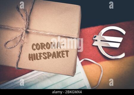 PHOTOMONTAGE, package with inscription Corona aid package on Germany flag  /  FOTOMONTAGE, Paket mit Aufschrift Corona-Hilfspaket auf Deutschlandfahne - Stock Photo