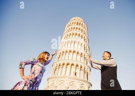 Loving couple takes selfie photo on stick and camera against background of leaning Tower Pisa, Italy. Travel concept. - Stock Photo