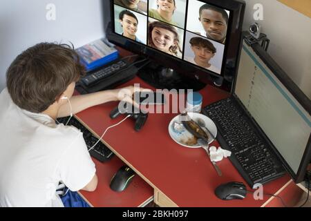 Teenage boy video chatting on the computer with friends at home - Stock Photo