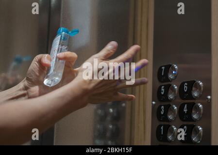 Man's hands applying alcohol sanitizer gel - Stock Photo