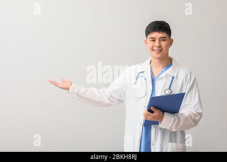 Male Asian doctor with clipboard showing something on light background - Stock Photo